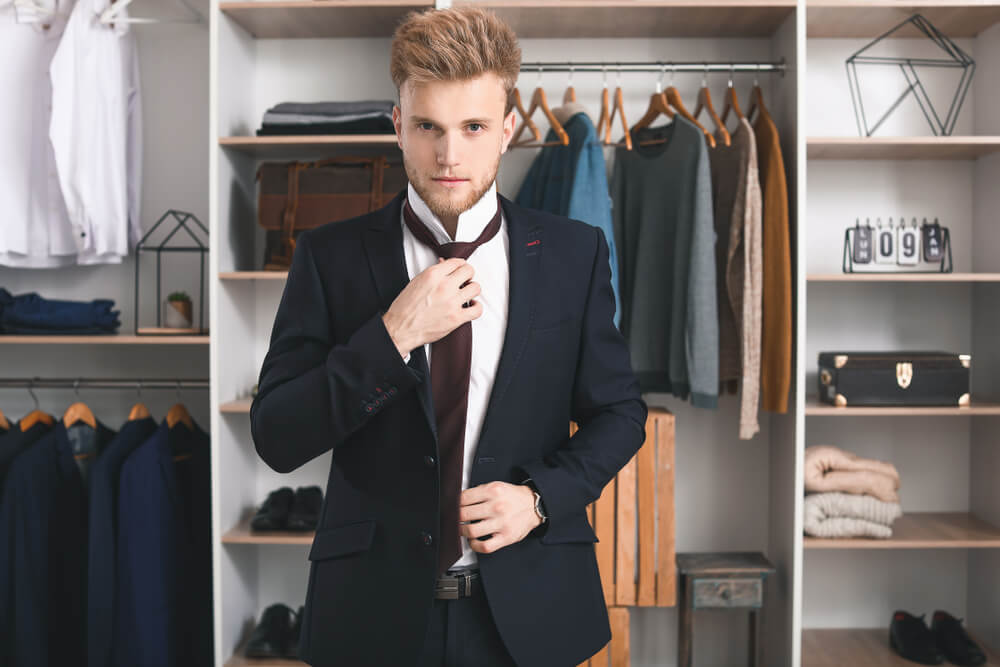 man trying a suit in front of his wardrobe