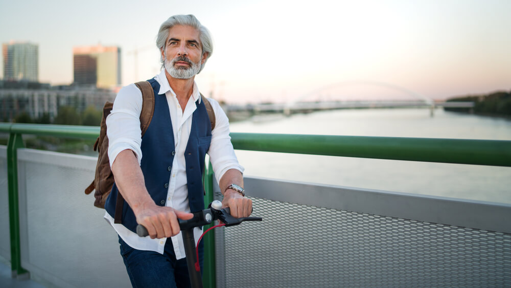 man wearing a waistcoat while holding a scooter