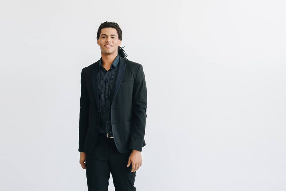 man wearing black suit with blue shirt