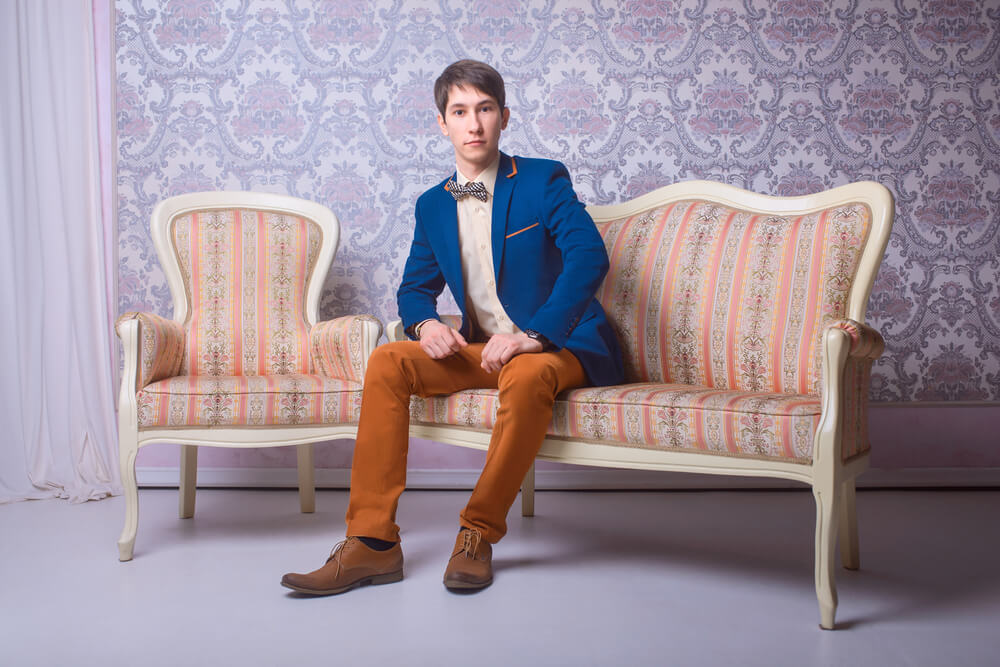 man wearing a suit with unbuttoned jacket sitting on a sofa
