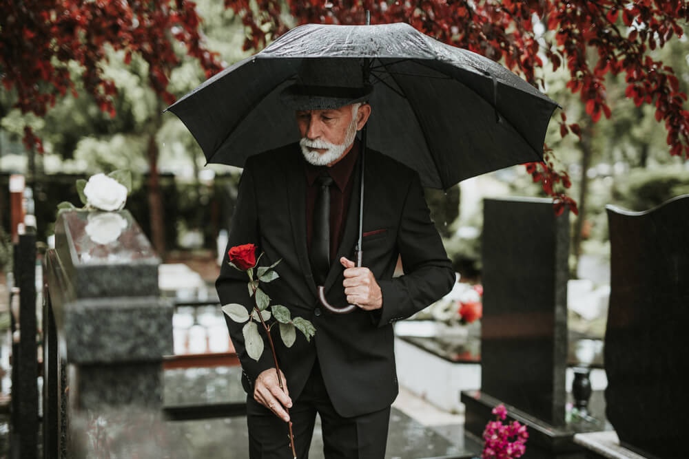older man attending a funeral in a black suit