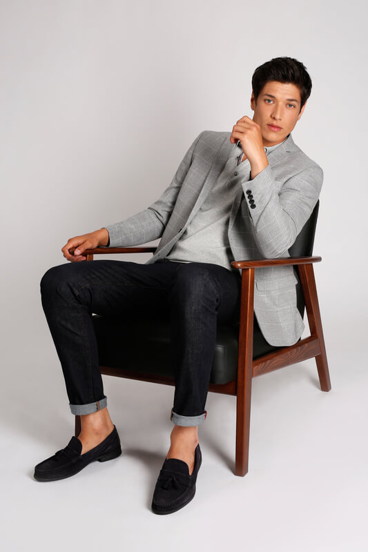 man wearing polo with suit sitting in a chair