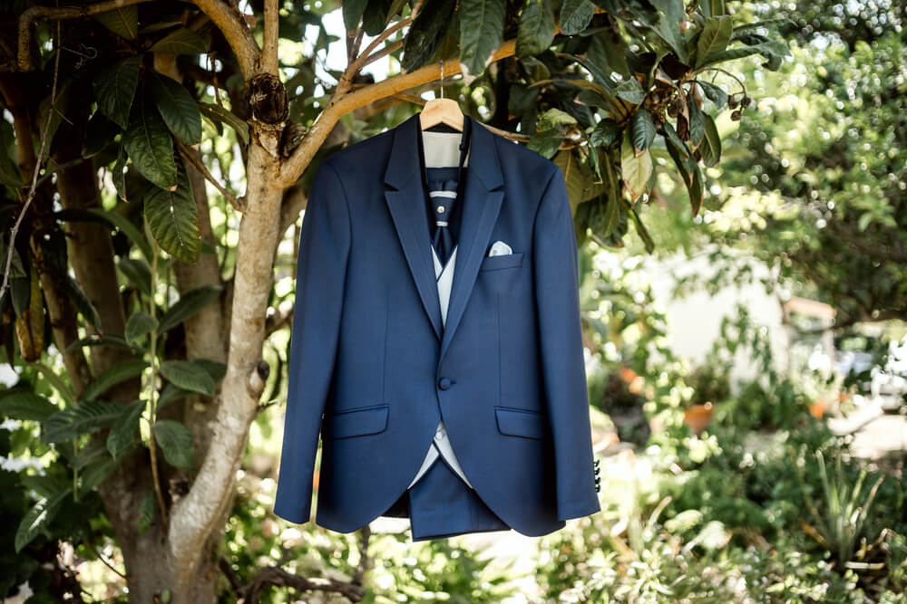 navy suit with grey waistcoat hanging from a tree