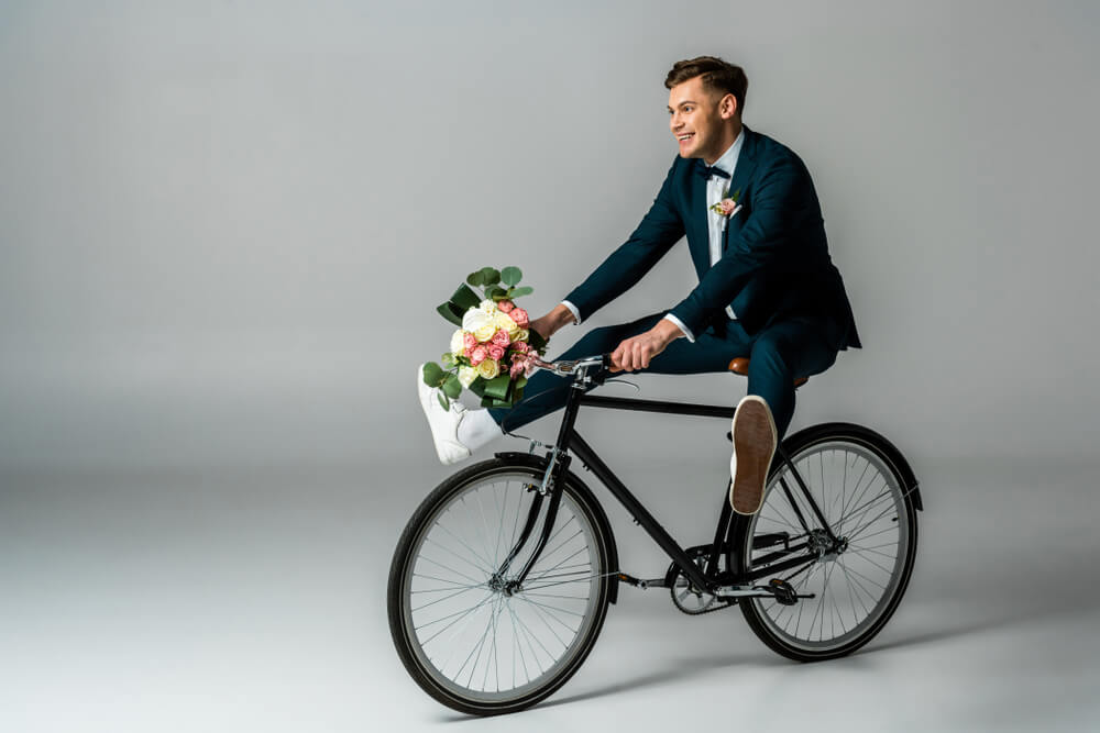 man in casual suit riding a bike